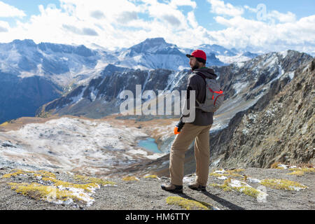 Hiker looking at view while standing on top of mountain - Stock Photo