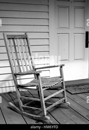 Weathered, vintage rocking chair on the porch of a white house. - Stock Photo