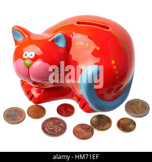 Red piggy bank in the form of a cat with different euro coins scattered around it - Stock Photo