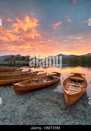 A fiery sunset over boats on the shore of Derwentwater at Keswick in the Lake District - Stock Photo