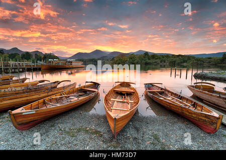 A fiery sunset over boats on the shore of Derwentwater at Keswick in the Lake District in Cumbria - Stock Photo