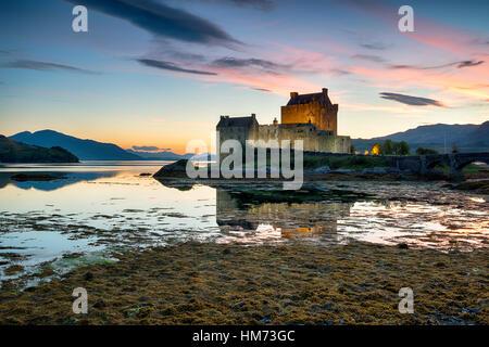 Sunset over Eilean Donan castle in Scotland - Stock Photo