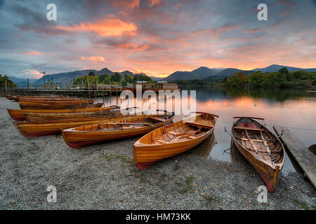 Sunset over wooden boats on the shores of Derwentwater at Keswick in the Lake District national park in Cumbria - Stock Photo