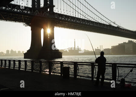 Man fishing from the East River Esplanade with a view of the Brooklyn waterfront under the Manhattan Bridge - Stock Photo