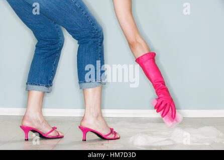 Legs and hand of mature woman wearing high heels and cleaning floor - Stock Photo