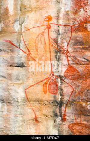 Aboriginal rock painting of a Mabuyu figure hunting in a gallery on a sandstone escarpment. - Stock Photo