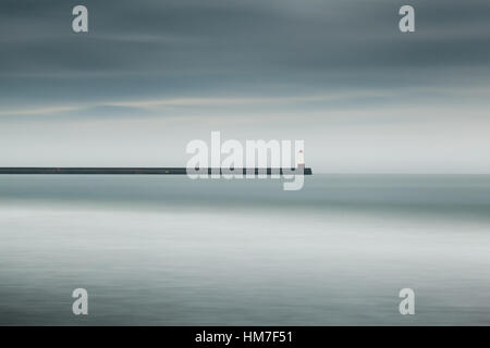 Long exposure of the long pier and lighthouse at Berwick-upon-Tweed from Spittal beach on a rainy day in Northumberland - Stock Photo