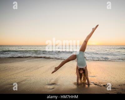 Girl (8-9) doing cartwheel on beach - Stock Photo