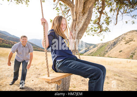 Father with daughter (8-9) sitting on swing - Stock Photo