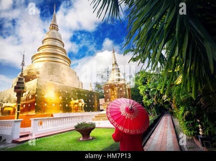 Woman tourist with red traditional Thai umbrella near Golden Stupa at temple Wat Phra Singh in Chiang Mai, Thailand - Stock Photo