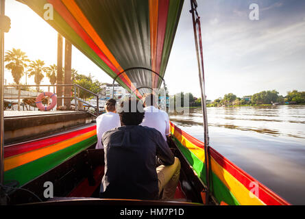 Tourist sitting in long-tail boat cruise by Chao Phraya river in Ancient city Ayutthaya at Sunset, Thailand - Stock Photo