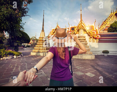Woman in hat and purple t-shirt leading man by hand to the Wat Pho famous temple in Bangkok, Thailand. - Stock Photo
