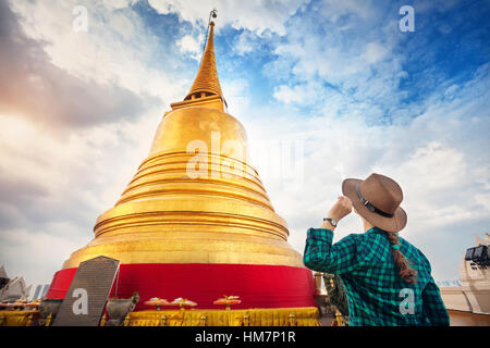 Tourist woman in hat and green checked shirt looking at big golden Stupa in Wat Saket temple in Bangkok, Thailand - Stock Photo