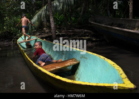 Kids play in one of the local boats used by the Ngobe Indians as their main form of transport, sheltered under a makeshift lean-to. Channel to entranc Stock Photo