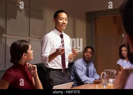Asian businessman standing to address colleagues at meeting - Stock Photo