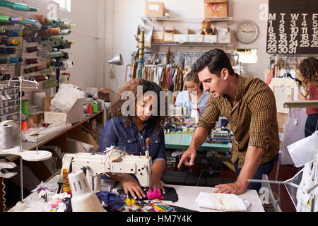 Colleagues in discussion at a clothes manufacturing studio - Stock Photo