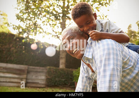Young black boy climbing on his grandfather's back in garden - Stock Photo
