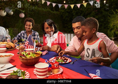 Multi generation black family members at a 4th July barbecue - Stock Photo