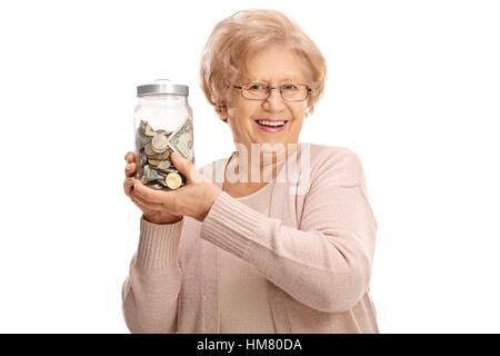 Happy mature lady holding a jar filled with money isolated on white background - Stock Photo