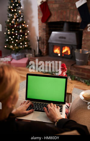 Woman Using Laptop In Room Decorated For Christmas - Stock Photo
