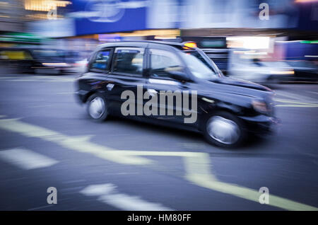 A London taxi in Piccadilly Circus - Motion Blur - Stock Photo