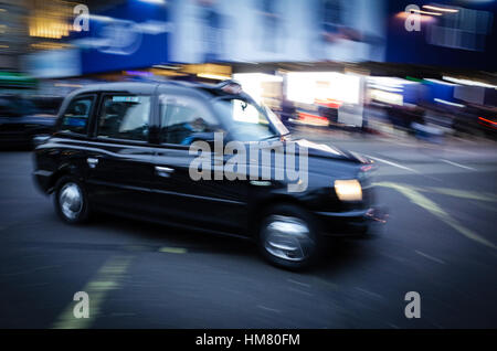 London Taxi Black Cab in Piccadilly Circus - Motion Blur - Stock Photo
