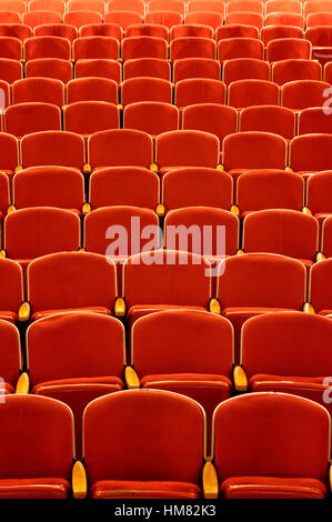 Empty theater seats in vibrant red with wooden arm rests, a concert hall stage view of no audience or patrons, old - Stock Photo