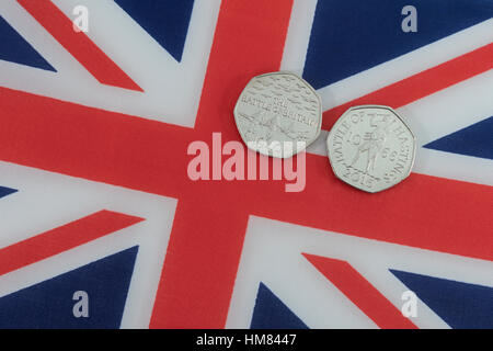 Union Jack with 50p commemorative coins - Battle of Britain and Battle of Hastings - Stock Photo