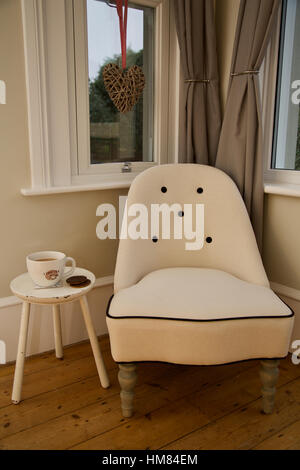 Traditional victorian cream chair in corner by window at home with table with cup of tea and biscuit ready to take - Stock Photo