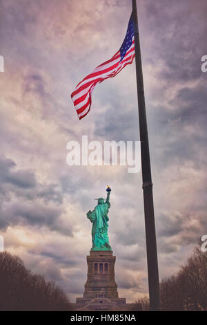 Rear view of Statue of Liberty with American flag - Stock Photo