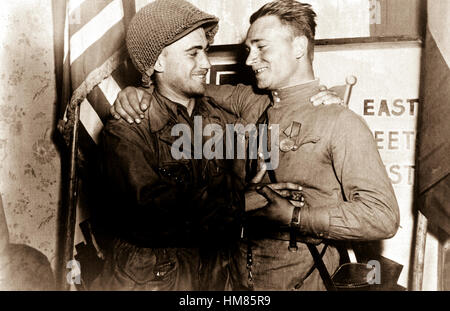Happy 2nd Lt. William Robertson and Lt. Alexander Sylvashko, Russian Army, shown in front of sign (East Meets West) - Stock Photo