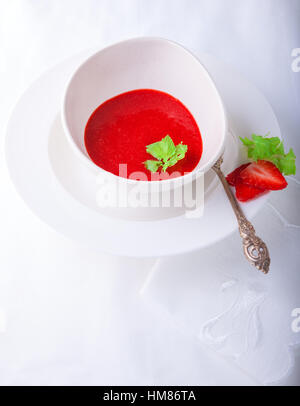 Fresh Strawberry soup with mint on white background. - Stock Photo