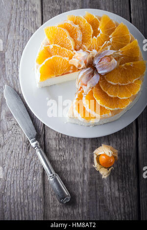 Cheesecake decorated with oranges and physalis on a table - Stock Photo