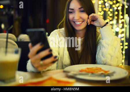 Woman typing write message on smart phone in a modern cafe. Cropped image of young pretty girl sitting at a table - Stock Photo