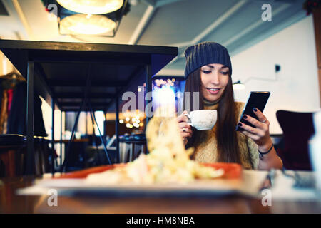 Portret of young female reading sms on the phone in cafe. Tonned. Selective focus. - Stock Photo