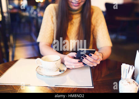 Woman typing text message on smart phone in a cafe. Cropped image of young woman sitting at a table with a coffee - Stock Photo