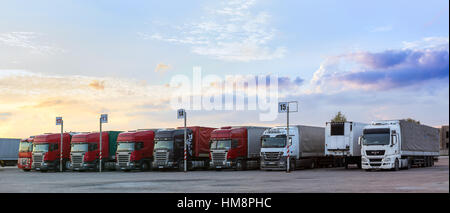 Narva, Estonia - August 20, 2016: Scania, MAN & Mercedes heavy trucks loaded with goods trailers, parked in waiting - Stock Photo