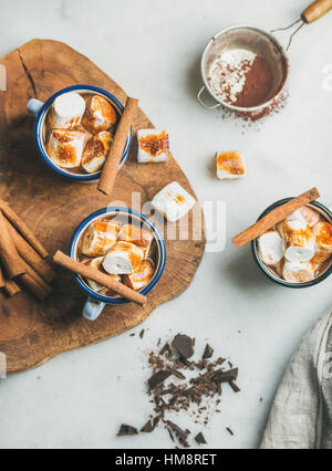 Hot chocolate in enamel mugs with cinnamon and roasted marshmallows - Stock Photo