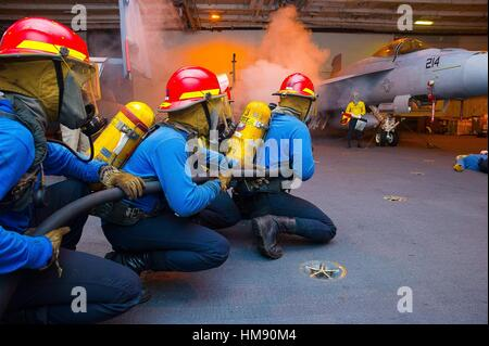 TIMOR SEA (July 7, 2015) Sailors fight a simulated class bravo fire in the hangar bay of the Nimitz-class aircraft - Stock Photo