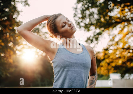 Portrait of healthy young woman stretching her neck outdoors. Caucasian fitness model warming up in park. - Stock Photo