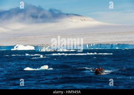 Zodiac with tourists cruising through the icebergs, Brown Bluff, Tabarin Peninsula, Antarctica, Polar Regions - Stock Photo