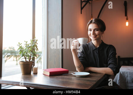 Picture of amazing cheerful young woman sitting at the table in cafe and looking at camera while drinking coffee. - Stock Photo