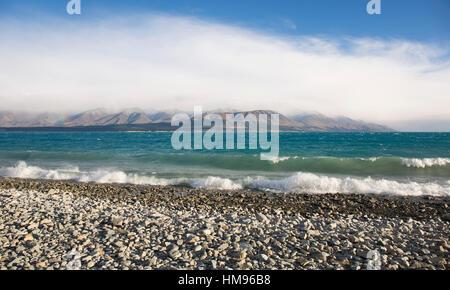 View from rocky shoreline across the stormy waters of Lake Pukaki, near Twizel, Mackenzie district, Canterbury, - Stock Photo