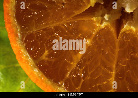 Juicy orange up close on a green background - Stock Photo