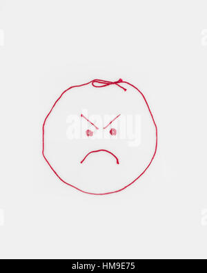 Concept, conceptual. An angry face shaped from red yarn. Cutout. - Stock Photo