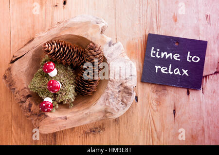 pinecones on wooden table and chalkboard with the words Time To Relax - Stock Photo