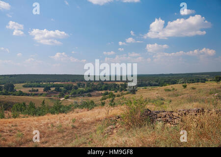 Rural landscape, a ruined fence made of natural stone, bushes, pasture, in the background the river, the forest - Stock Photo
