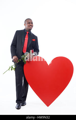 African man in black suite holding red rose. - Stock Photo