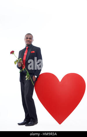 Young handsome african man holding red rose, flower for his girlfriend for Valentine Day. Male in black suite and - Stock Photo