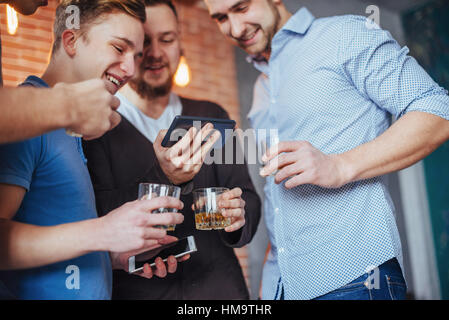 Cheerful old friends communicate with each other and phone watch,  glasses of whiskey in pub. Concept  entertainment - Stock Photo